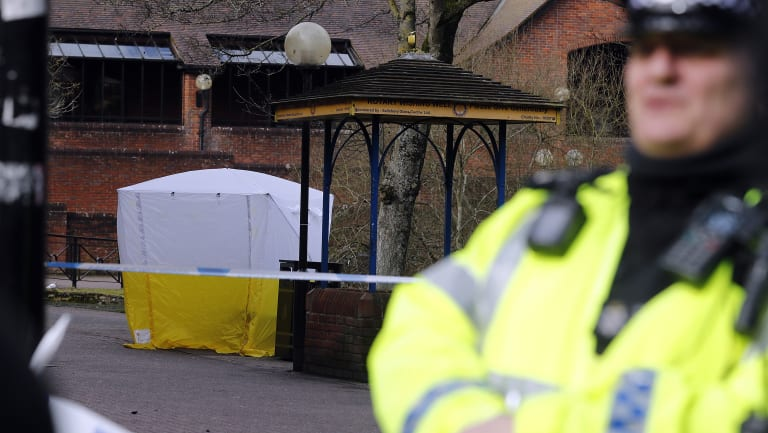 A police officer secures the area where Skripal and his daughter were found critically ill on the park bench.