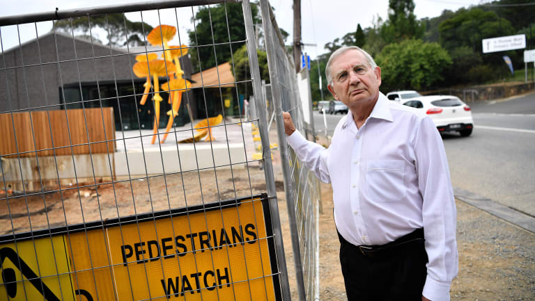 Local GP Dennis Gration in front of the unfinished Belgrave community hub.