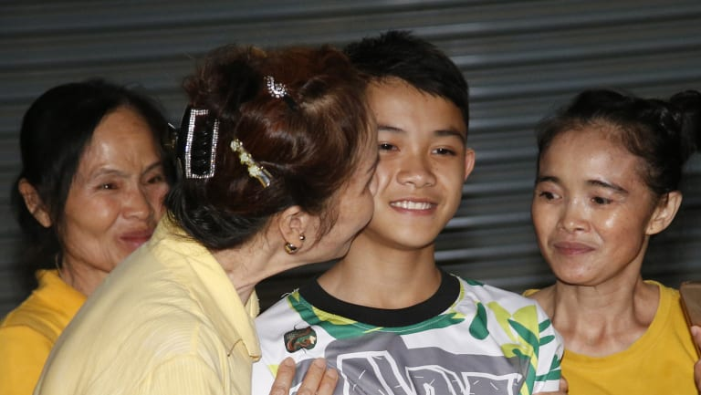 "Relatives of Duangpetch ""Dom"" Promthep, one of the boys rescued from the flooded cave in northern Thailand, greet him as he arrives home on Wednesday."
