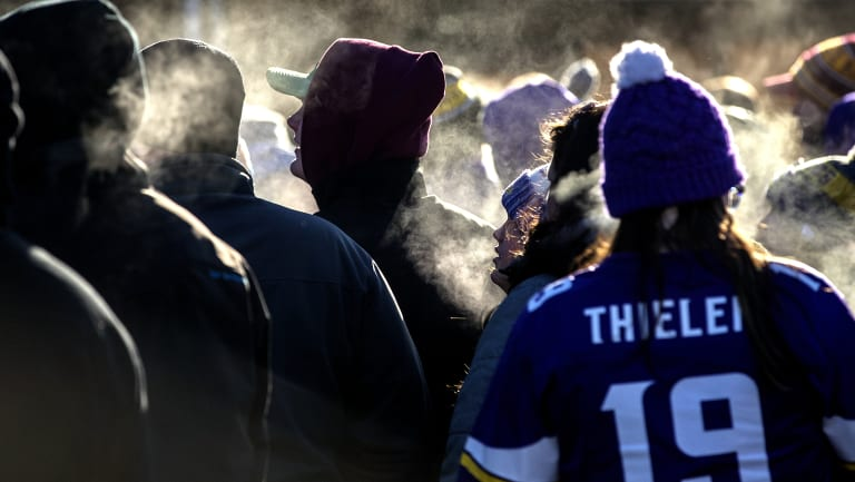 Fans stand in line in subzero temperatures to enter a stadium to watch an NFL football game in Minneapolis.