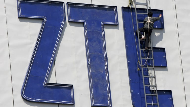 A worker installs the logo of ZTE, a Chinese communications company in Nanjing, China.