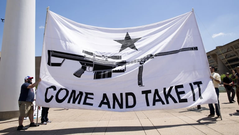 "Demonstrators hold a large banner that reads ""Come And Take It,"" during a pro-gun rally on the sidelines of the National Rifle Association (NRA) annual meeting in Dallas, Texas."