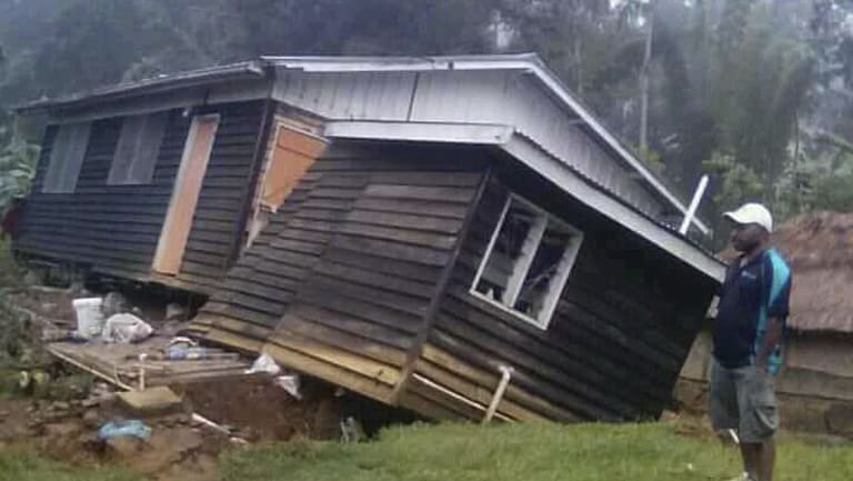 A man views a house that collapsed in the strong earthquake in Halagoli, Hela. PNG.