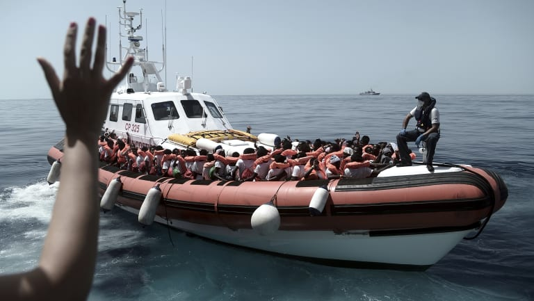 Migrants board an Italian Coast Guard ship after being transferred from the Aquarius to be taken to Spain on Tuesday.