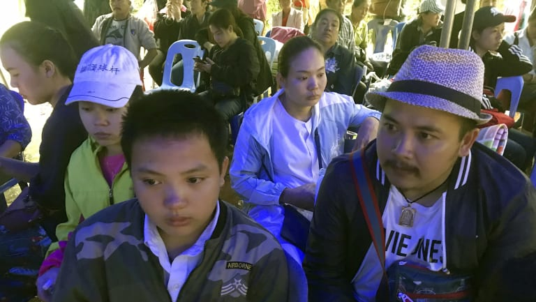 Songpol Kanthawong, 13, sits with his father Noppadon Kanthawong, right, in a tent outside the cave where his soccer team and coach are trapped.