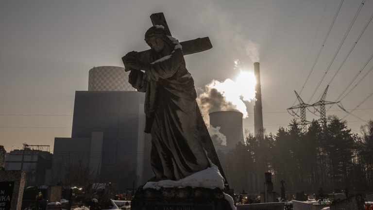 A statue, adorning a tomb, is seen at the cemetery of Bedzin, Poland, in the vicinity of the city's coal-fuelled power plant.