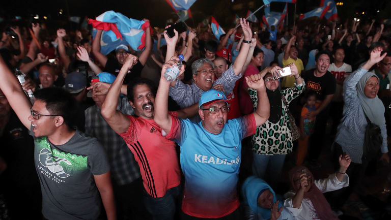 Opposition party supporters cheer and wave their party flags after Mahathir claimed victory.