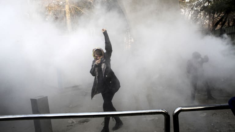 A student protests at Tehran University while a smoke grenade is thrown by anti-riot Iranian police.