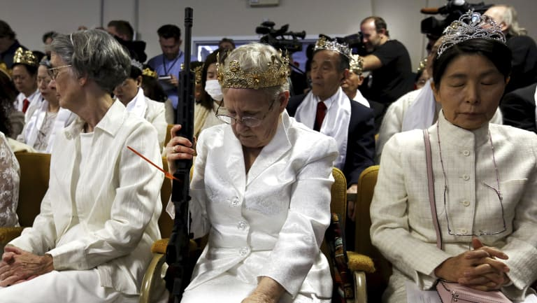 A woman wears a crown and holds an unloaded weapon as she bows her head during services at the World Peace and Unification Sanctuary, in Newfoundland, Pennsylvania.