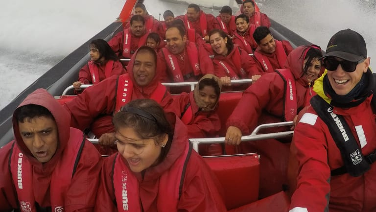 Indian tourists enjoy a jet boat ride on Sydney Harbour
