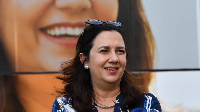 Queensland Premier Annastacia Palaszczuk is seen standing next to the media bus.