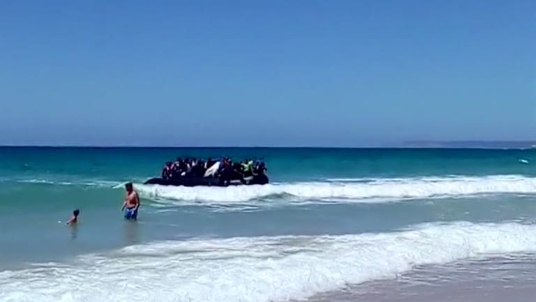 A rubber dingy carrying migrants approaches the beach at Cadiz, southern Spain last year.