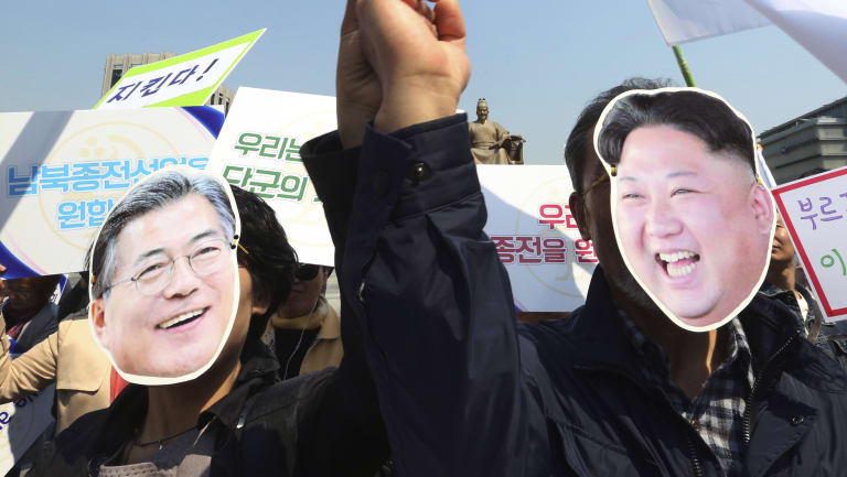 South Korean activists wearing masks of South Korean President Moon Jae-in, left, and North Korean leader Kim Jong-un welcome the planned summit between the leaders.