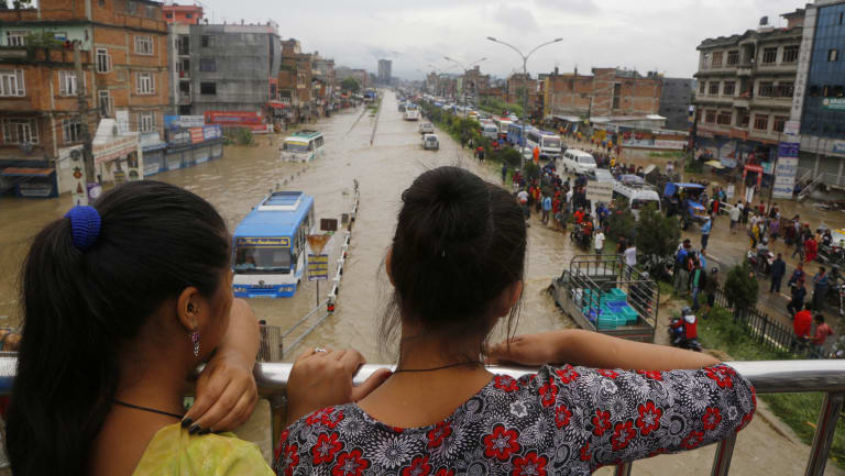 Nepalese women look at a flood area in Bhaktapur.