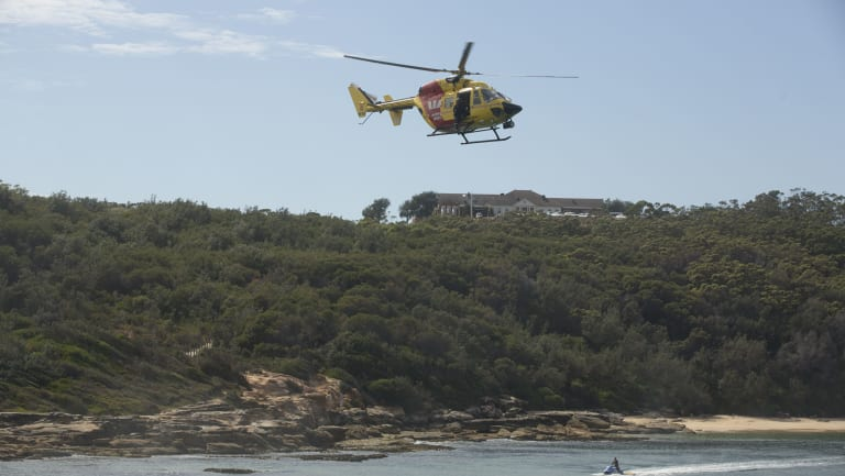 The Westpac rescue helicopter and surf lifesavers search for a shark at Congwong Beach in Sydney's south, where a woman was bitten on Friday night.