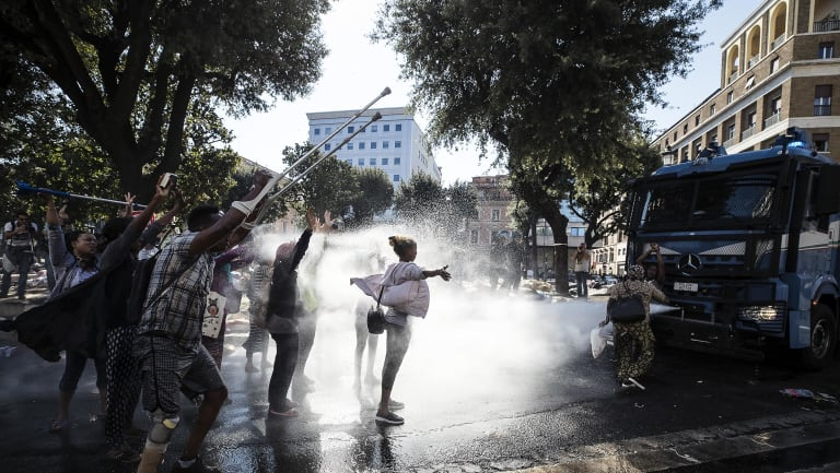 Italian police use water cannons to disperse migrants in downtown Rome last year.