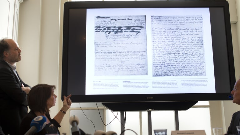 A video shows the text underneath two taped off pages from Anne Frank's diary.