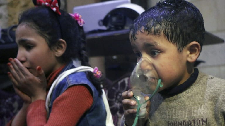 This image released early on Sunday, April 8, 2018 by the Syrian Civil Defence White Helmets, shows a child receiving oxygen through respirators following an alleged poison gas attack in the rebel-held town of Douma.