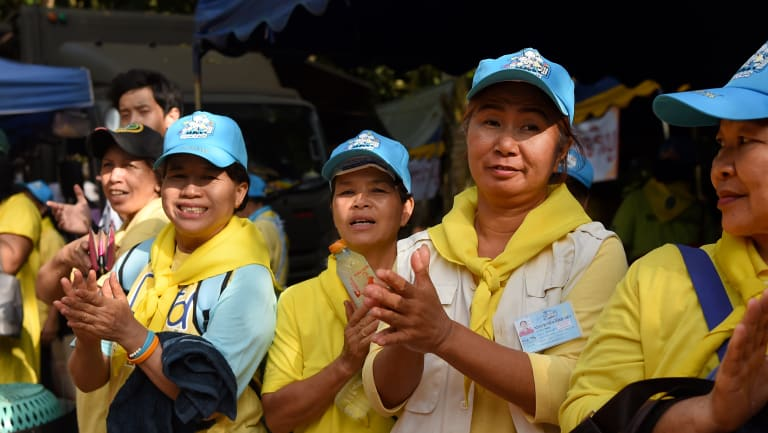 Thai volunteers applaud firefighters at the rescue base camp.