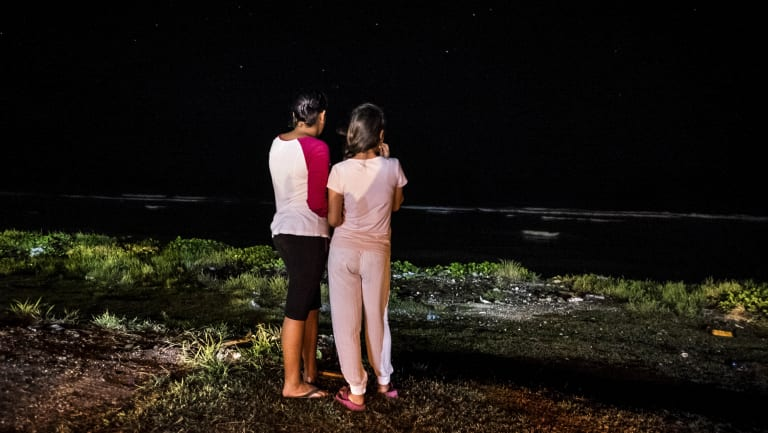 Two asylum-seekers look at the ocean in front of the community based camp for families with children on the island of Nauru.