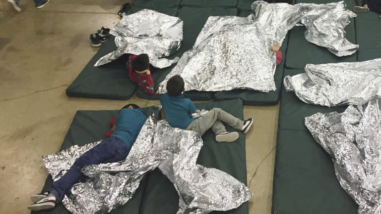Teens who've been taken into custody on the US-Mexico border rest in one of the cages at a facility in McAllen, Texas.