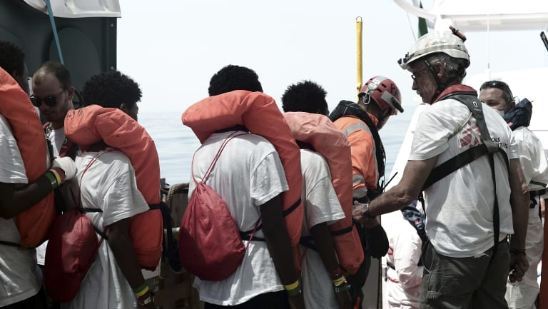 Migrants are transferred from the Aquarius to an Italian coast guard vessel at sea so they can be taken to Spain.