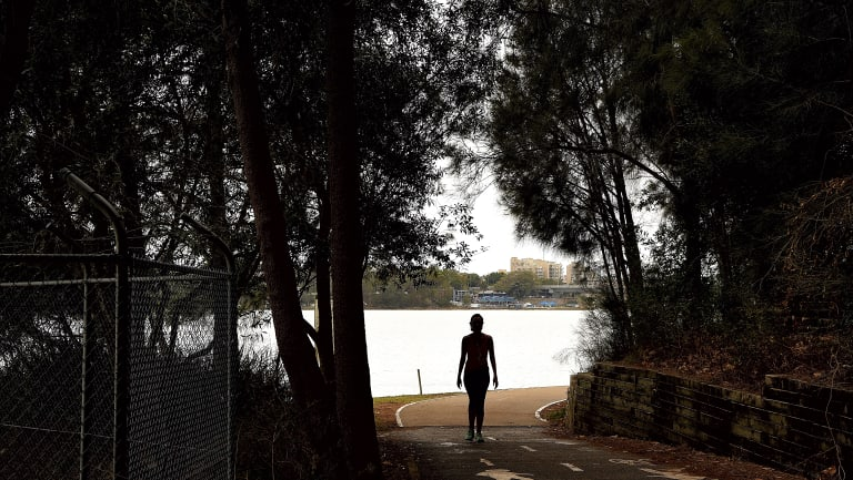 A woman walks along a path near Leichhardt Oval on the Bay Run in Lilyfield.