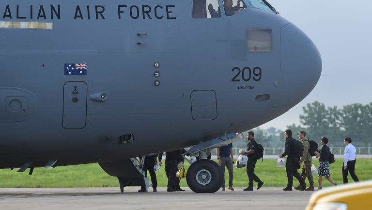 The Australian Federal Police dive team and support staff walk over the tarmac at Chiang Rai airport to board an Australian RAAF plane bound for Canberra.