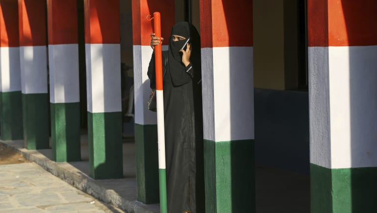A Muslim woman talks on her mobile phone as she stands between pillars painted in the colours of the Indian national flag after casting her vote at a polling station in Bangalore.