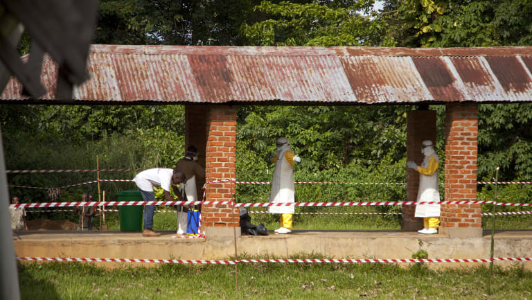 Health workers are sprayed with chlorine after leaving the isolation ward to diagnose and treat suspected Ebola patients, at Bikoro Hospital in Bikoro, the rural area where the Ebola outbreak was announced in early May in Congo.