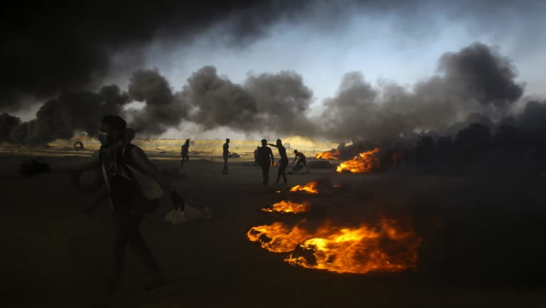 Palestinian protesters burn tires during a protest at the Gaza Strip's border with Israel.
