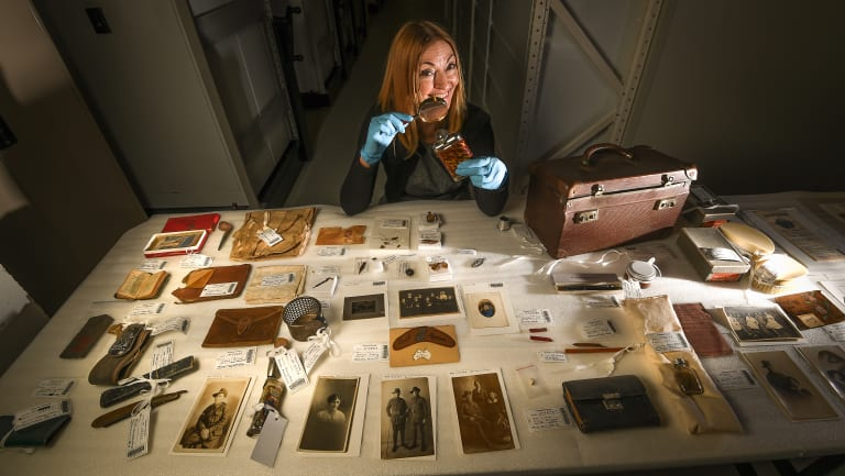 Melbourne Museum senior curator Deb Tout-Smith with the contents of Ward's suitcase.