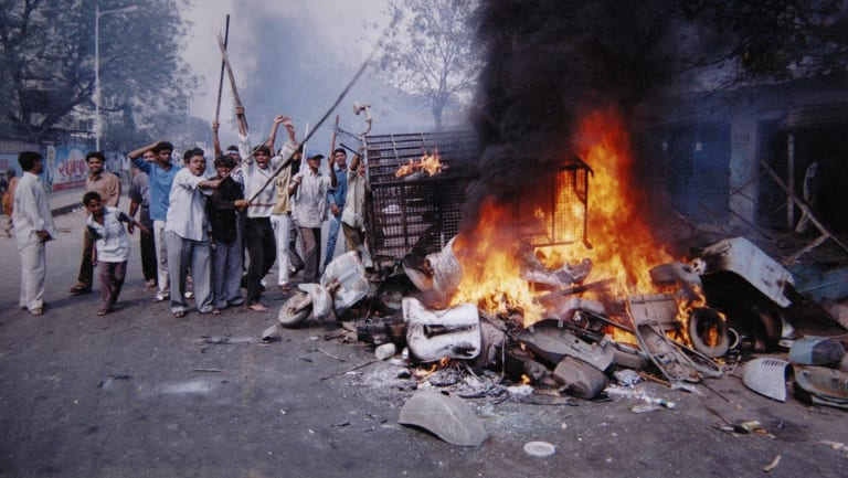 A mob sets fire to vehicles and other goods in Ahmadabad, India in 2002. Sectarian violence erupted as retaliation after 59 Hindus were killed when a train car burst into flames in Godhra.