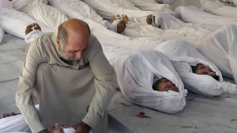 A Syrian man mourning over a body after an alleged poisonous gas attack fired by government forces, according to activists, in Douma, Syria in 2013.