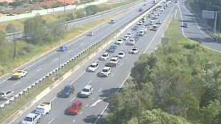 A north-facing traffic camera captures the southbound congestion on the M1 in Robina.