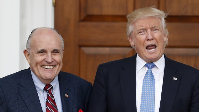 Then-President-elect Donald Trump calls out to media as he and former New York Mayor Rudy Giuliani pose for photographs in November 2016.