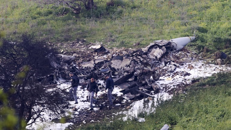 Israeli security stands around the wreckage of an F-16 that crashed in northern Israel, near kibbutz of Harduf.