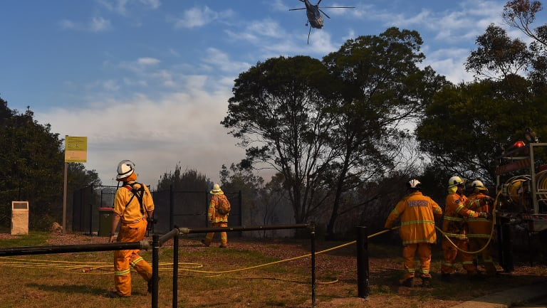 RFS crew members watch a helicopter move into position to drop water on the fire front.