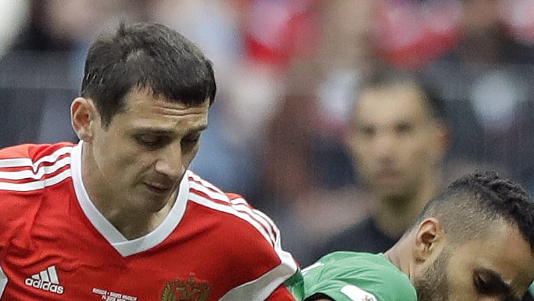 Russia's Alan Dzagoev, left, and Saudi Arabia's Mohammed Alburayk challenge for the ball during the group A match between Russia and Saudi Arabia which opened the 2018 soccer World Cup.