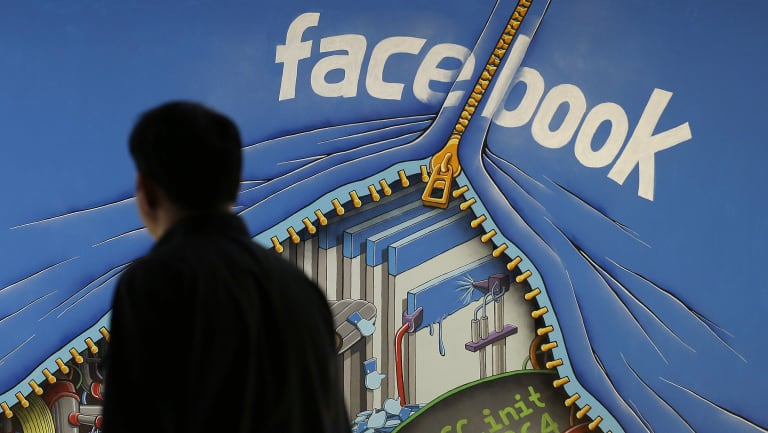 A man walks past a mural in an office on the Facebook campus in Menlo Park, California.