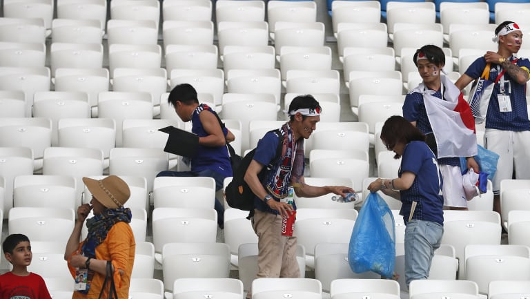 Fair play in the stands: Japanese fans clean up after themselves post-game.
