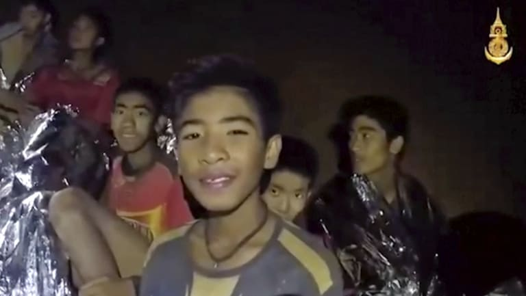 Thai boys smile as a Thai Navy SEAL medic helps the injured in the cave earlier in the week.