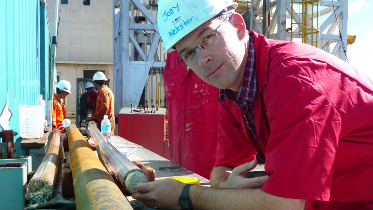 Associate Professor Jody Webster on board a drilling vessel with a fossil core from the Great Barrier Reef.