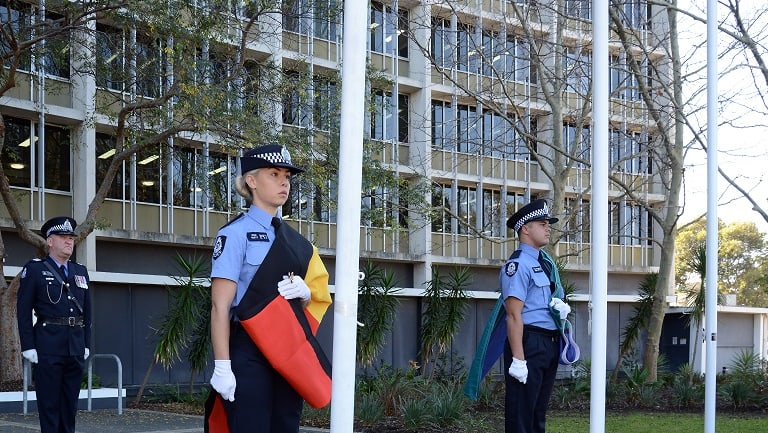 Aboriginal Cadet Graduates, Constable Maddison Ugle and Constable Jacob Collard, before raising the Aboriginal and Torres Strait Islander flags.
