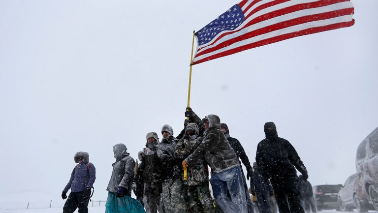 Military veterans huddle together to hold a United States flag against strong winds during a march to a closed bridge outside the Oceti Sakowin camp to protest the Dakota Access oil pipeline in Cannon Ball, ND.