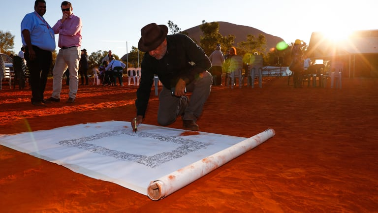 False dawn?: Noel Pearson signs a canvas on which the Uluru Statement from the Heart was later painted in May.