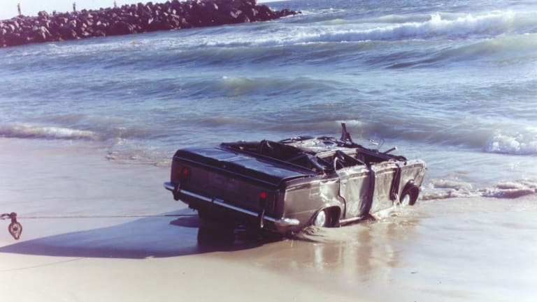 The car is towed back onto the beach.