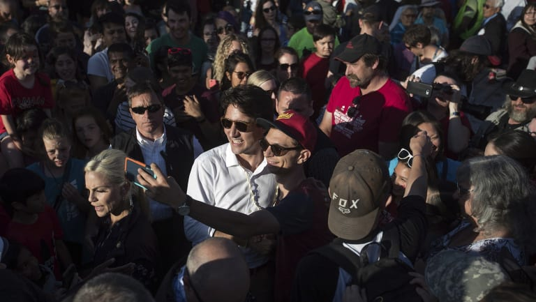 Canadian Prime Minister Justin Trudeau, centre in white, poses for a selfie with a man at a Canada Day barbecue event in Dawson City, Yukon.