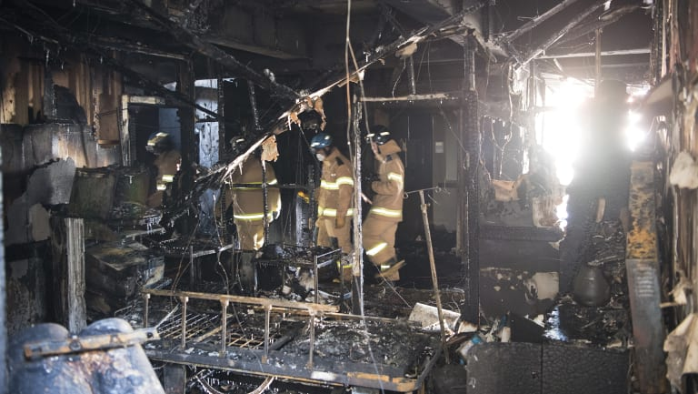 Firefighters inspect a burnt hospital after a fire in Miryang, South Korea.