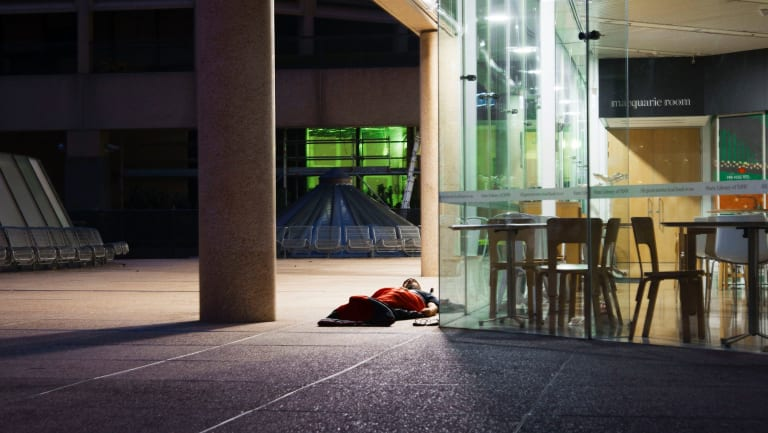 A homeless man spends the night outside the State Library of NSW.